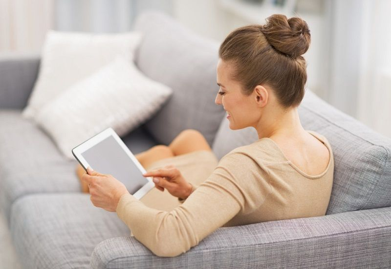 woman on sofa with ipad tablet