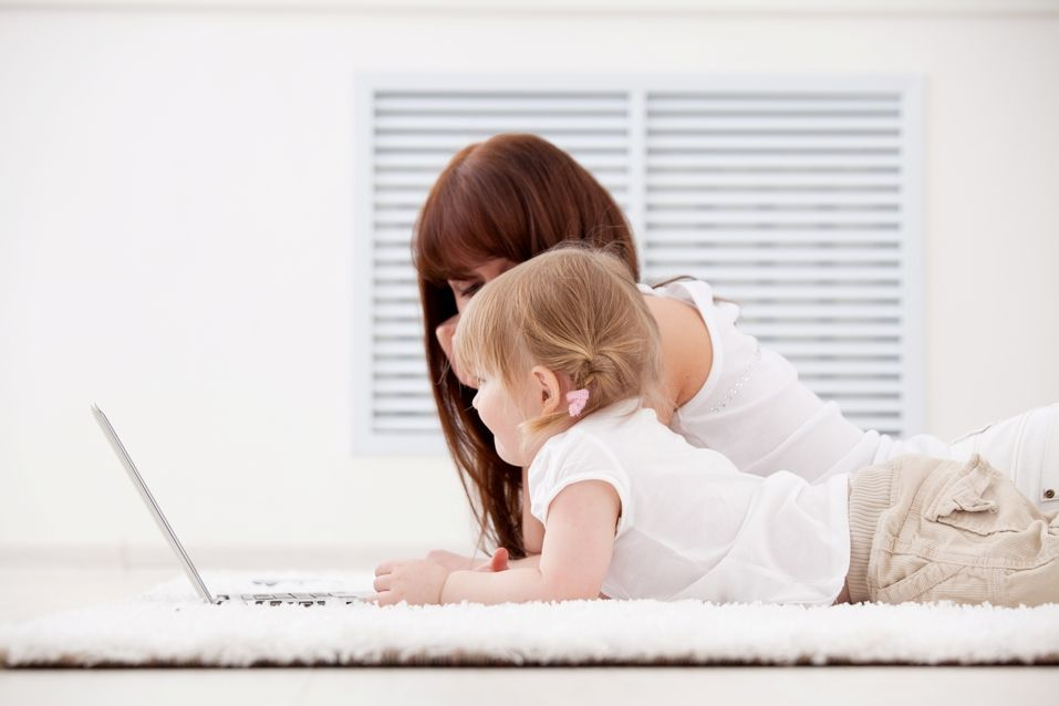 Mother and baby on carpet with laptop