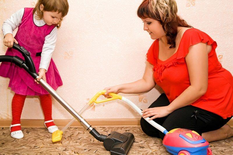 mom and daughter vacuuming carpet