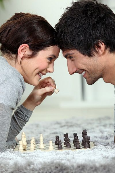 Couple playing chess on carpet