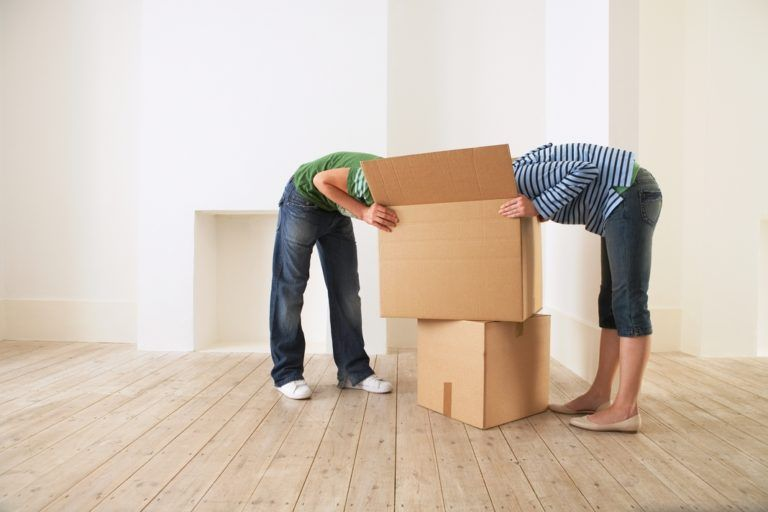 couple moving - heads in cardboard boxes